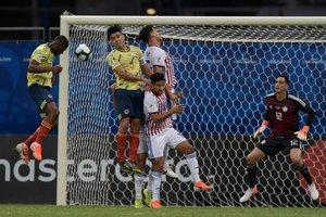 El colombiano Jefferson Lerma (L) encabeza el balón mientras el arquero paraguayo Roberto Fernández observa durante el partido de fútbol de la Copa América en el estadio Fonte Nova Arena en Salvador, Brasil.