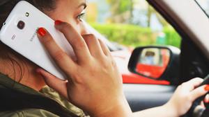 Mujer usando el teléfono móvil al volante