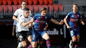 El defensa del Valencia, Hugo Guillamón, y el centrocampista del Huesca, Pedro Mosquera, luchan por el balón