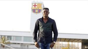 Ezekiel Bassey, posando junto al escudo del Barcelona