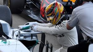 Hamilton, arrodillado en frente de su coche