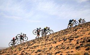 Los competidores llevan sus bicicletas a lo largo de una duna de arena durante la Etapa 2 de la 14ª edición de la carrera de ciclismo de montaña Titan Desert 2019 entre Merzouga y Ouzina.