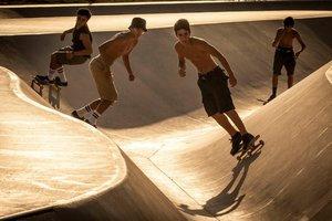 Jóvenes practican skate durante el atardecer, cerca de la zona de la playa de la Mar Bella de Barcelona.