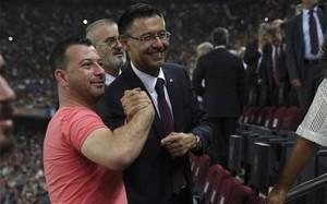 El presidente del FC Barcelona, Josep Maria Bartomeu, fotografiándose con un aficionado en el palco del Camp Nou