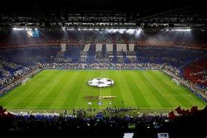 Los jugadores de Barcelona (d) y del Lyon (i) durante los himnos antes del partido por los octavos de final de la Liga de Campones de la UEFA entre el FC Barcelona y el Olympique de Lyon, este martes, en el estadio Groupama de Decines-Charpieu