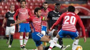 El central del Granada Germán pugna por un balón con un rival