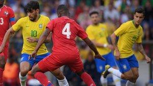 Paquetá disputa un balón ante la mirada de Coutinho.