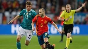 Iniesta controla ante Müller en el partido de Düsseldorf