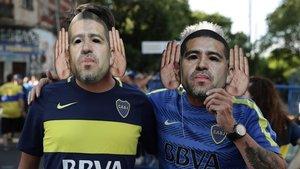 Seguidores de Boca Juniors usando caretas de Juan Román Riquelme antes de un partido en la Bombonera