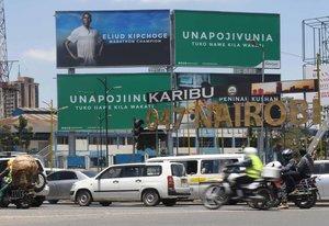 Una valla publicitaria erigida en Nairobi por un proveedor de telefonía móvil local muestra una foto de Eliud Kipchoge, el campeón olímpico y mundial de maratón de Kenia, es fotografiado mientras los automóviles pasan en Nairobi.