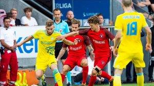Munksgaard, de rojo, disputa un balón a Konzen
