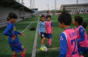 Las niñas juegan al fútbol durante una sesión de entrenamiento en su escuela en Shanghai.