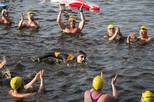 El ex campeón del mundo holandés Maarten van der Weijden (C) es aclamado cuando llega a la meta en su segundo intento de nadar a lo largo del Elfstedentocht, un viaje de más de 200 kilómetros, en Leeuwarden, Países Bajos.
