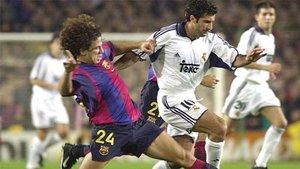 Puyol y Figo disputan un balón la noche en la que el luso regresó a Barcelona por primera vez tras su traición