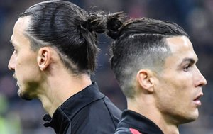 Cristiano Ronaldo (D) y Zlatan Ibrahimovic cruzan antes del partido de fútbol de ida de la semifinal de la Copa de Italia (Coppa Italia) entre el AC Milan y el Juventus Turín en el estadio San Siro de Milán.