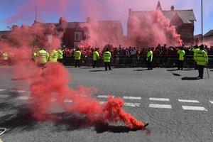 Los seguidores del Liverpool dejan bombas de humo rojo mientras esperan la llegada del autobús del equipo antes del partido de la Premier League entre el Liverpool y el Wolverhampton Wanderers en Anfield en Liverpool.