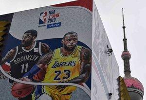 Un trabajador retira una pancarta promocional de un edificio para el partido de pretemporada de la Asociación Nacional de Baloncesto (NBA) el 10 de octubre en China entre los Brooklyn Nets y Los Angeles Lakers en Shanghai.